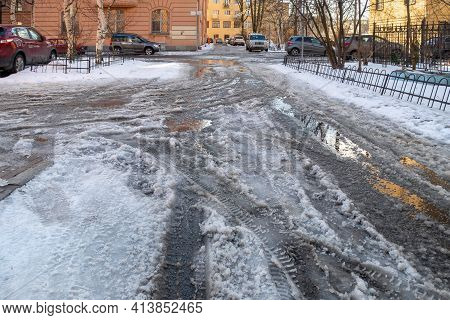 St. Petersburg, Russia - March 22, 2021: Slush, Melting Snow And Puddles On The City Street In Sprin