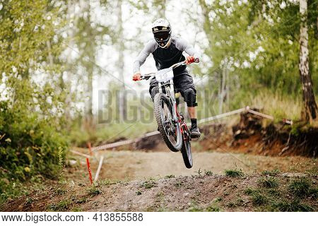 Athlete Rider Downhill Jump Over Hill In Forest