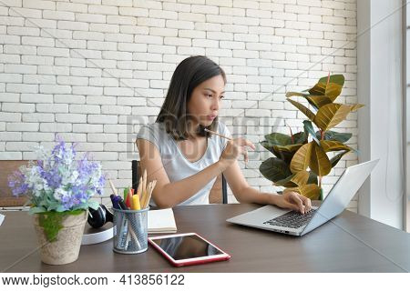 Smiling Young Asian Woman Wear Casual Clothing While Sitting At Big Wooden Table In Modern Kitchen,