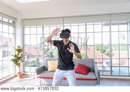 Young Asian Man Getting Experience With Vr Virtual Reality Headset Or 3d Glasses In Living Room At H