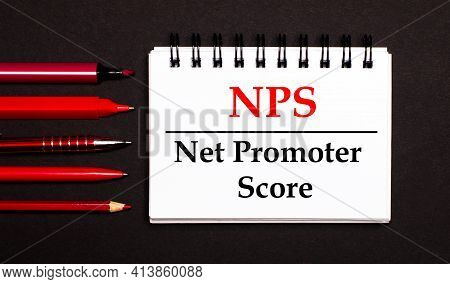 A White Notepad With The Text Nps Net Promoter Score, Written On A White Notepad Next To Red Pens, P