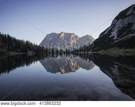 Sunrise Mirror Reflection Panorama Of Zugspitze Mountain Massif In Clear Calm Transparent Alpine Lak