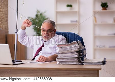 Old male employee in blood transfusion concept