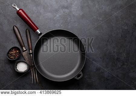 Frying pan, utensils and ingredients on kitchen table. Top view flat lay with copy space
