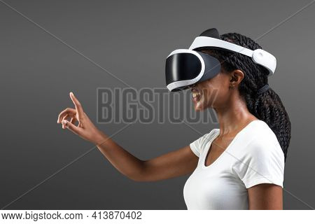 Woman with VR headset touching invisible screen futuristic technology