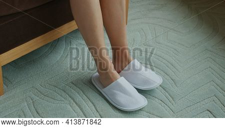 Woman wear slipper from bed at hotel room