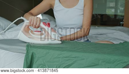 Woman iron clothes with iron on ironing board