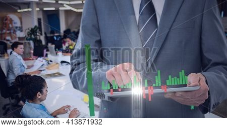 Composition of digital statistics over businessman using tablet in office. global business and finance, connection and networking concept digitally generated image.