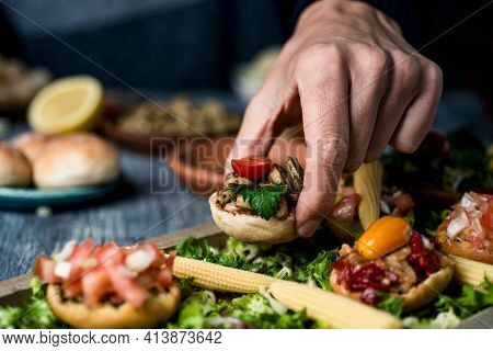 closeup of a young caucaisan man picking an appetizer from a wooden tray with some different vegan appetizers, with different toppings, placed on a gray table