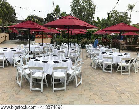 NEWPORT BEACH, CALIFORNIA - JULY 12, 2019: Worker setting up an outdoor event area at the Hyatt Regency Newport Beach.