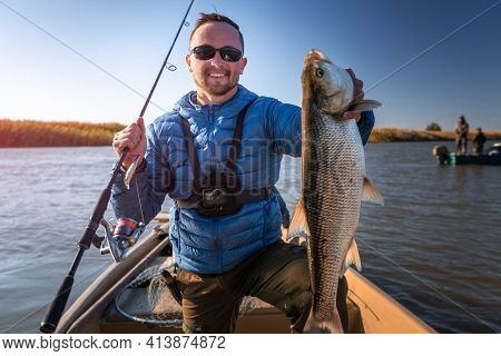 Angler with Asp fish. Amateur fisherman holds the asp fish and stands in the boat with river on the background