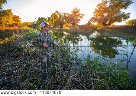 Angler on a river. Fisherman stands with fishing rod and fishing on a small river with natural autumn background
