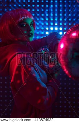 DJ girl. Attractive girl with bright glitter make-up and pink hair poses with disco balls in neon lights. Night party. Disco style.
