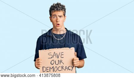 Young handsome man holding save our democracy protest banner scared and amazed with open mouth for surprise, disbelief face
