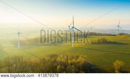 Wind Turbines Or Wind Mills Farm In The Field At Sunlight.