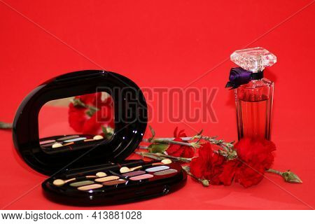 Perfume Set On A Wooden Table Is Decorated With A Bouquet Of Carnations. The Background Is Red. Beau
