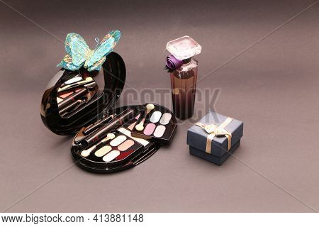 Perfume Set On A Wooden Table Is Decorated With A Bouquet Of Carnations. The Background Is Black. Be