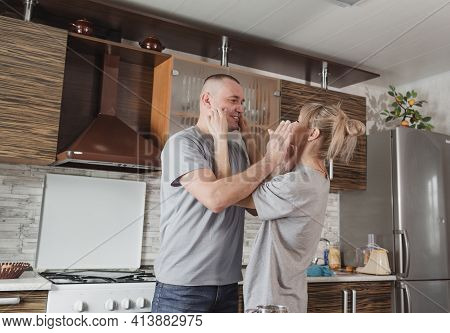A Happy Married Couple Indulges In Smearing Each Other With Flour While Cooking In The Kitchen. Happ