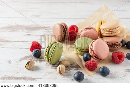 Variety Of French Macaroons With Berries Such As Raspberry And Blueberry Over Wooden Background. Fre