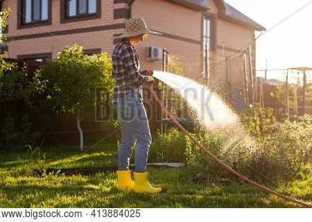 Caucasian Woman Gardener In Work Clothes Watering The Beds In Her Vegetable Garden On Sunny Warm Sum