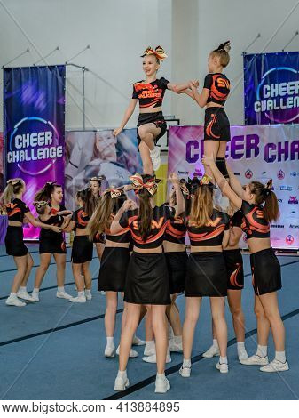Moscow, Russia - December 22, 2019: Cheerleader Teen Girls In Sports Uniform Perform A Trick, Well-c