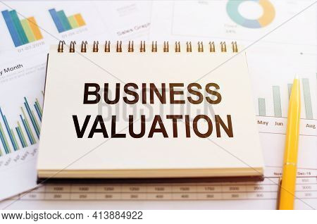Business Valuation - Written On Notepad On Financial Charts And Graphs With Yellow Pen.