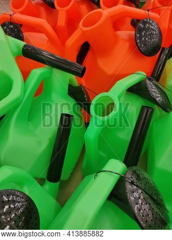 Red And Green Watering Cans With Black Spouts And Diffusers On The Store Counter