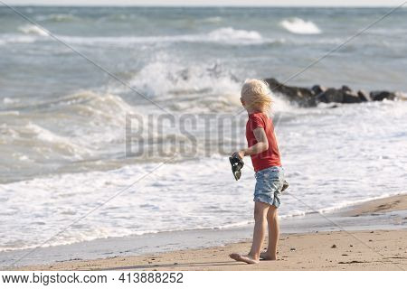 Fair-haired Boy Walks Along The Seashore And Looks At The Waves. Happy Childhood.