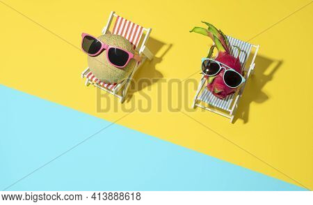 Above View With Cantaloupe And Dragon Fruits Sitting In Miniature Beach Chairs With Sunglasses On. S