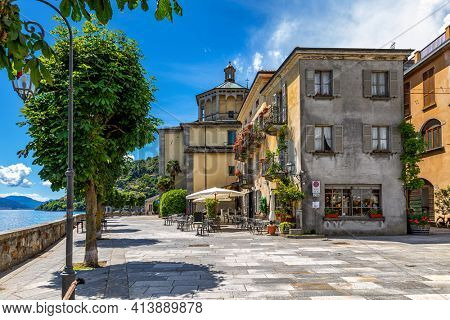 View of promenade along old vintage houses and Lake Maggiore under blue sky in Cannobio - small town in Piedmont, Northern Italy.