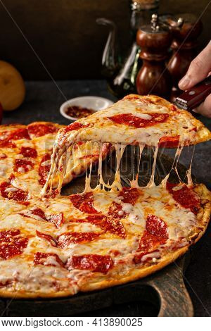 Pepperoni Pizza With A Slice Taken Out With Cheese Pull