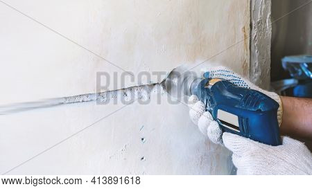 Worker Drills A Hole For An Electrical Outlet In A Concrete Brick Wall. Repair Of Electrical Wiring.