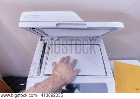 A White Or Caucasian Man Is Working In The Office Making Photocopies On A White Copier With The Top