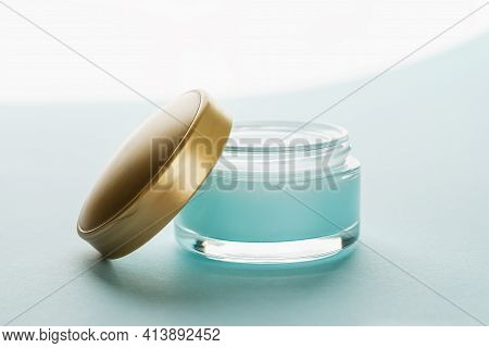 Moisturizing Facial Gel In An Open Jar With Golden Lid On A Light Blue Background. Glass Container O