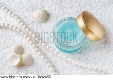 Moisturizing Facial Gel In An Open Jar With Golden Lid, Pearl Beeds And Few Sea Shell On A White Tow