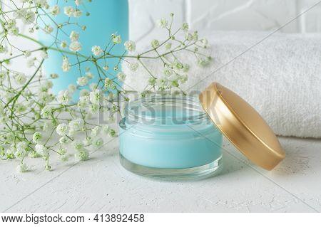 Open Jar Of Blue Moisturizing Facial Gel Near White Terry Towel In A Bathroom. Hydrating Face Cream