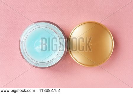 Moisturizing Facial Gel In An Open Jar And Golden Lid On A Pastel Pink Background. Glass Container O