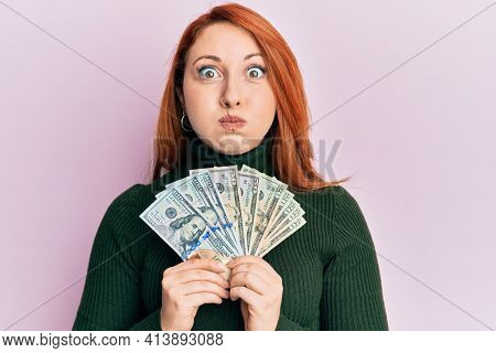 Beautiful redhead woman holding dollars close to face puffing cheeks with funny face. mouth inflated with air, catching air.