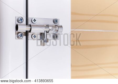 Aluminum Manual Latch Bolt Installed On A White Lacquered Aluminum Carpentry Door Inside A Home