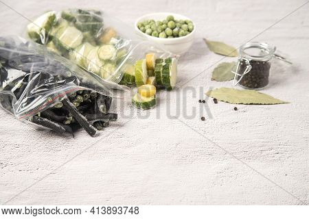 Bags Of Frozen Vegetables String Beans And Zucchini As Well As Frozen Green Peas On A Light Backgrou