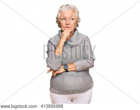 Senior grey-haired woman wearing casual winter sweater with hand on chin thinking about question, pensive expression. smiling with thoughtful face. doubt concept.