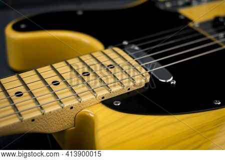 Electric Guitar Strings On Neck And Frets. American Classic Lacquered Guitar In Yellow Tones.