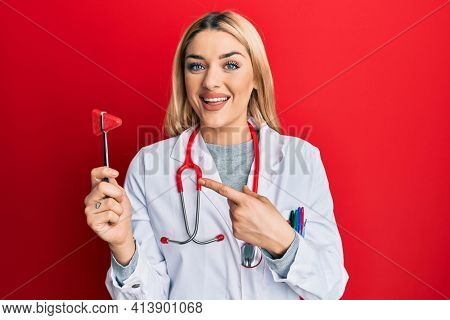 Young caucasian woman wearing doctor uniform holding medical reflex hammer smiling happy pointing with hand and finger