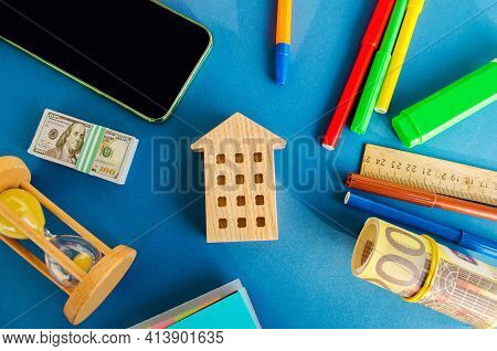 Miniature Wooden House, Money And Hourglass On A Blue Background. Real Estate Concept. Affordable Ho