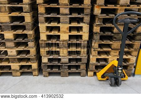 Hand Pallet Truck With Stack Of Wooden Pallets. Warehouse Equipment. Transportation Of Goods In Stoc
