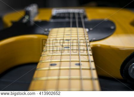 Close-up Of The Mast, Frets And Strings Of A Classic Electric Guitar, In Yellow And Black, Bright On