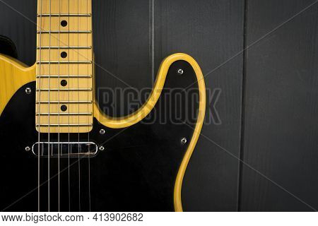 Details Of A Classic Electric Guitar In Yellow And Black, With Its Frets, Strings, Neck And Micropho