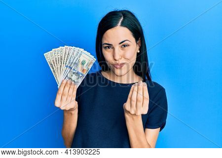 Beautiful young woman holding dollars doing money gesture with hands, asking for salary payment, millionaire business