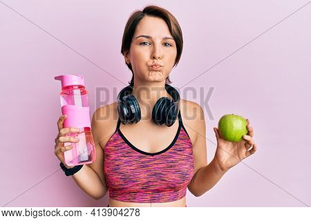 Young brunette woman with short hair wearing sportswear holding water bottle and apple puffing cheeks with funny face. mouth inflated with air, catching air.