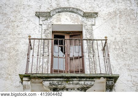 Window With Access To Old Balcony And Wrought Iron Fence Wrought By The Passage Of Time On A Facade